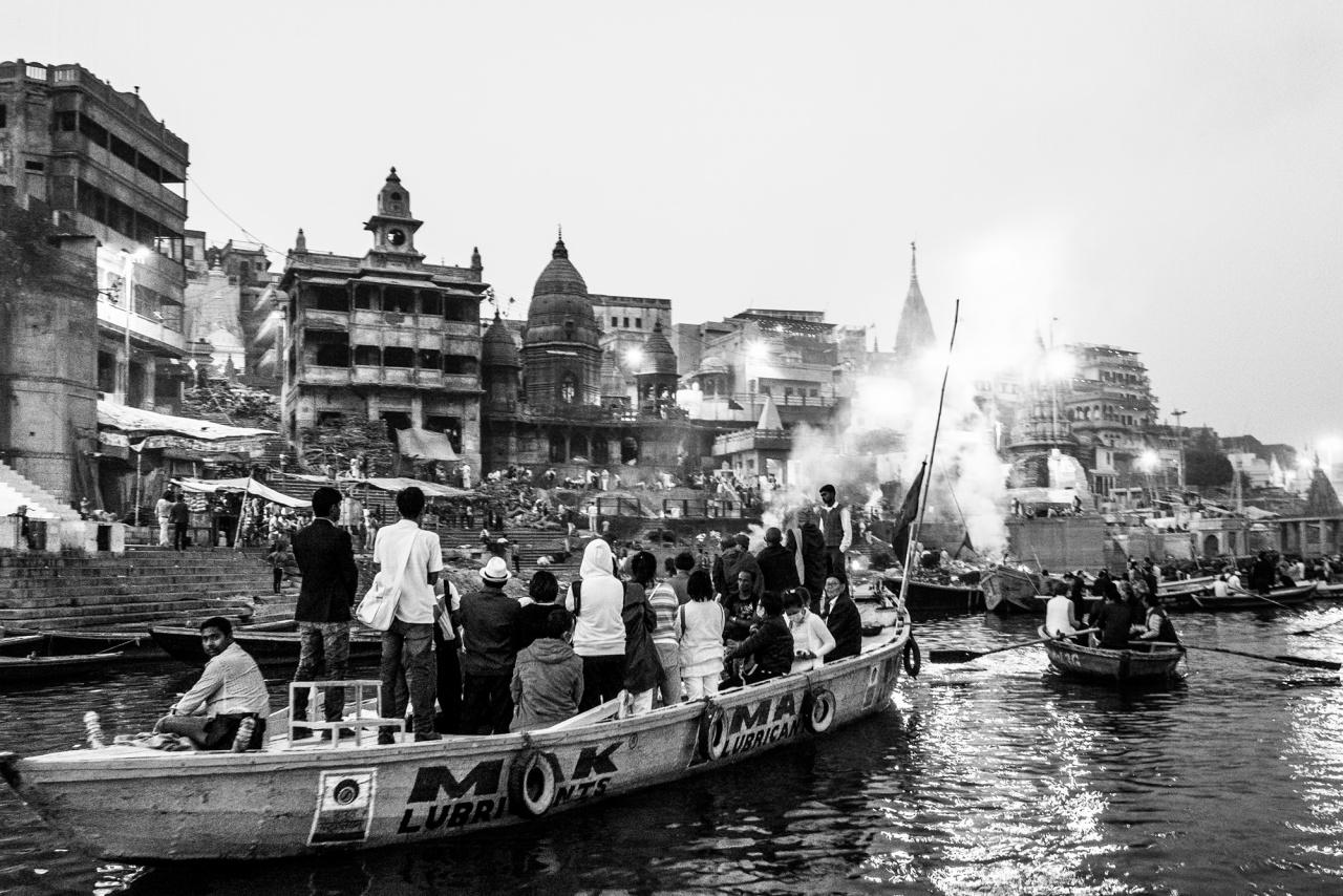 The show must go on - Barconi di turisti solcano le acque del Gange nei pressi del Manikarnika Ghat dal quale quale si levano le fiamme e i fumi delle pire funerarie - Varanasi, 2016